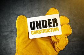 picture of overhauling  - Under Construction on Business Card Male Hand in Yellow Leather Construction Working Protective Gloves Holding Card with Rounded Corners - JPG