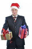 Young Businessman In Santa Hat Offering A Gift To You. Isolated On White Background