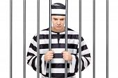 A Sad Prisoner In Jail Holding Bars