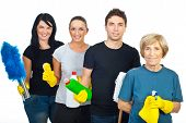 image of house cleaning  - Cheerful team of four people holding cleaning products isolated on white background - JPG