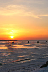 picture of ice fishing  - sunset over the ice fishing shacks in the harbour - JPG