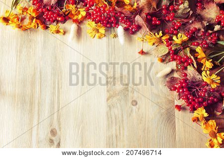 poster of Autumn background with seasonal autumn nature berries and autumn flowers on the wooden background. Vintage autumn still life with free space. Autumn composition made of seasonal autumn berries and flowers. Autumn background