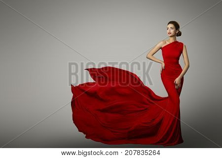 poster of Fashion Model in Red Beauty Dress Sexy Woman posing evening Gown Flying Silk Tail over gray background