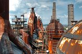 foto of blast-furnace  - A wide shot of a decaying rusting steel plant with several furnaces and blast chambers - JPG
