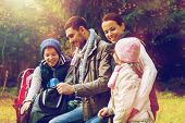 travel, tourism, hike and people concept - happy family sitting on bench and drinking hot tea from c poster
