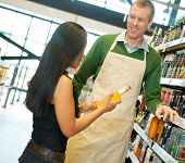 Woman standing with smiling store worker while holding drink bottle in grocery store