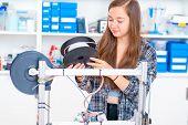 Schoolgirl prints 3d model from plastic on 3d printer poster