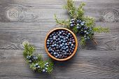 Wooden bowl with seeds of juniper. Juniper branch with berries. Juniper berries in a bowl with a spr poster