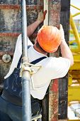 builder worker at construction site checking formwork with level measuring equipment