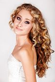 Beautiful young blonde woman with long curly hair in white fashion sequin top isolated on white back