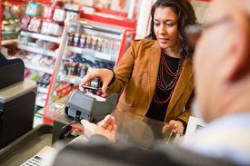 picture of mobile-phone  - A young woman paying for grocery purchase with a mobile phone - JPG