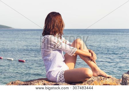 poster of Traveler Girl Relaxing On Beach. Young Girl Traveler Relaxing In Vacation. Traveler Relaxing On Rock