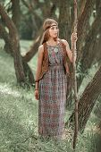 Young Hippie Woman With A Long Stick Walking Through The Forest poster