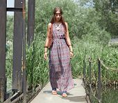 Beautiful Hippie Girl Walking On A Wooden Bridge In The Park poster