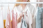 Clothing, Fashion, Style And People Concept - Woman Choosing Clothes At Home Wardrobe poster