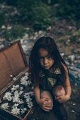 A Homeless Girl Is Sitting On A Garbage Dump Next To A Suitcase With Flowers Inside. The Concept Of  poster