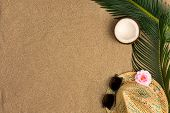 Beach Theme On The Sand Background. Palm Leaves, Coconut, Hat On The Sand. Top View. poster
