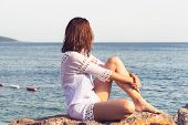 Traveler Girl Relaxing On Beach. Young Girl Traveler Relaxing In Vacation. Traveler Relaxing On Rock poster