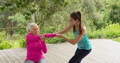Side view of beautiful Caucasian female trainer assisting active senior Caucasian woman to exercise  poster