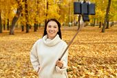season, technology and people concept - beautiful young happy woman taking picture by smartphone on  poster
