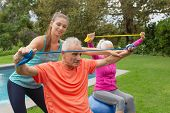 Side view of Caucasian female trainer assisting active senior Caucasian couple to exercise with resi poster