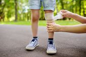 Mother Hands Applying Antibacterial Medical Bandage On Childs Knee After Falling Down. poster