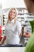 Female Pharmacist With Male Customer In Pharmacy Drugstore.
