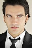 Detailed close-up portrait of a great looking male model in formal black suit and tie with bright bl