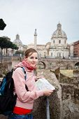 Pretty young female tourist studying a map at the Trajan's forum in Rome, Italy (dome of the Santiss