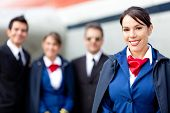 stock photo of cabin crew  - Flight attendant with cabin crew and an airplane at the background - JPG