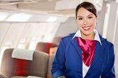 image of cabin crew  - Beautiful flight attendant in an airplane cabin smiling - JPG