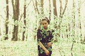 Girl Or Pretty Woman In Black Clothes Hiding In Fresh, Young, Green Tree Leaves In Spring Forest On  poster