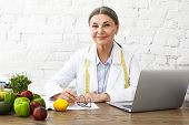 Indoor Shot Of Positive Smiling Caucasian Female Nutritionist In Her Sixties Working Online, Sitting poster