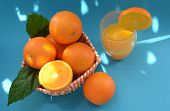 Oranges And Freshly Squeezed Orange Juice In A Glass Beaker With An Orange Slice On A Blue Backgroun poster
