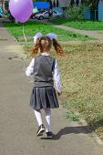 A Girl With Large White Bows On Her Head, A Beautiful Hairdo In A School Uniform, Is Walking Along T poster