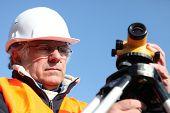 mature surveyor in construction site