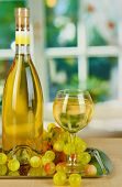 White wine in glass with bottle on salver on window background