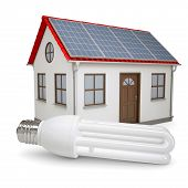 Energy Saving Lamp On The Background Of The House With Solar Panels