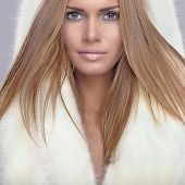 Fashion portrait of young pretty woman with fur