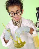 An adorable preschooler with wild hair and coke-bottle glasses delightedly  handling a bowl of yucky, green slime.