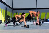 Gym man en vrouw push-up kracht pushup met dumbbell in een training