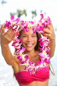 Hawaii woman showing flower lei garland of pink orchids. Beautiful smiling mixed race woman in bikin