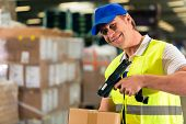 Warehouseman with protective vest and scanner, scans barcode of package, he standing at warehouse of freight forwarding company