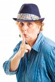 Middle aged woman puts her finger to her lips in a quiet or secret gesture.  Isolated on white.