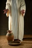Jesus standing with a jar of water and a bowl