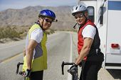 Two Senior men with bikes on road