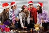 stock photo of christmas party  - Portrait of happy business people chatting while celebrating Christmas in office - JPG