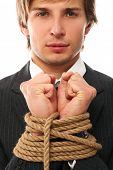 Handsome businessman hands tied with rope together