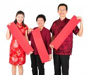 Happy chinese new year. Asian Chinese family holding red spring couplets, ready for text standing ov