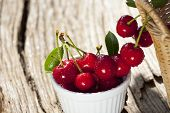stock photo of cherries  - Cherries with sparkling Water Drops are hanging on the side of a basket other Cherries are in a white Bowl on a old Wooden Table - JPG